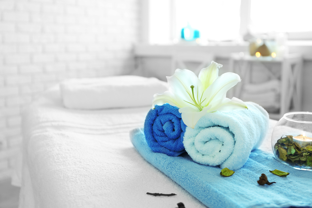 Spa table with blue towels and a white flower